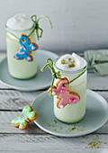 Matcha milk with milk foam decorated for Easter with butterfly biscuits