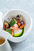 Seafood soup with salmon and clams decorated with flowers in bowl