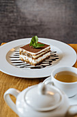 Chocolate tiramisu decorated with green and poured with syrup and tea