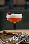 Roter Cocktail mit Schaum und Himbeerspiess