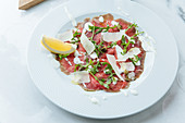Slices red beef on plate with pieces of fresh lemon with white sauce cheese and arugula