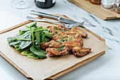 Fried golden chicken and herbs on wooden board with basil leaves