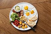 Englisches Frühstück mit Spiegeleiern, Speck, Toast und Gemüse