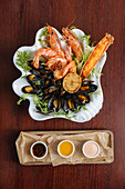 Grilled prawns and mussels with greens on plate with three sauces on side