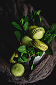 Homemade green macarons with mint on dark background