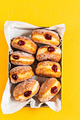 Donuts wth jam and sugar on yellow background