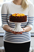 A woman holding a chocolate cake with oranges