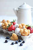 Small heart pancakes with berries and eggs in an egg box