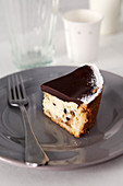 A slice of cheesecake with dark chocolate