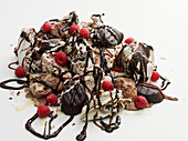 Ice cream piled with confectionery, chocolate sauce and raspberries