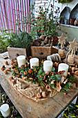 Ländliche Adventsdekoration mit Kerzen im länglichen Adventskranz, Schubladen mit Zapfen und Zweigen