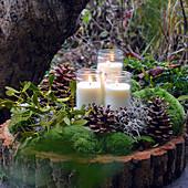 Winterliche Kerzendekoration mit Zapfen, Moos und Mistelzweig auf Holzscheibe