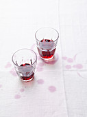 An arrangement of red wine with red wine stains on a white tablecloth