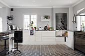 A spacious country house kitchen in black, white and grey with decorative floor tiles