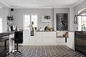 Großzügige Landhausküche in Schwarz, Weiß und Grau mit dekorativem Ornamentfliesenboden
