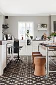 Vintage-Esstisch und Korkhocker in Landhausküche mit dekorativem Ornamentfliesenboden