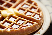 Whole belgian waffle with syrup and butter