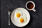 Two sunnyside eggs with pepper in a white plate with coffee in a white coffee cup on a black surface