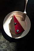 A piece of raspberry cake with two blueberries on a plate with a fork