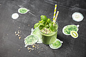 A green smoothie with spinach, apple, kiwi and basil