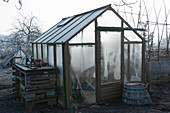 Gewächshaus mit gefrorenen Fensterscheiben im winterlichen Garten