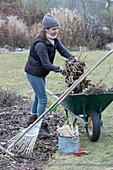 Frau räumt Gartenabfall in die Schubkarre