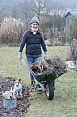 Frau mit Schubkarre voller Gartenabfall, Hund Zula
