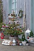 Nordmanntanne geschmückt mit Christbaumkugeln, Lichterkette und Kerzen, Sterne, Laternen und Birkenstämme als Deko