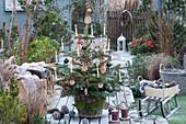 Nordmanntanne geschmückt mit Holzscheiben, Christbaumkugeln, Lichterkette und Kerzen, Brennholzstapel mit Fell und Decke als Sitzplatz