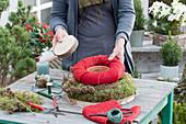 Selbstgemachte Mooskranztorte mit Kerze : Frau legt roten Filzkranz um einen Tontopf und Holzscheibe darüber