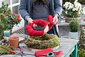 Selbstgemachte Mooskranztorte mit Kerze : Frau umwickelt Strohrömer mit rotem Filz