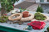 Zutaten für eine selbstgemachte Mooskranztorte mit Kerze : Strohrömer, Moos, Filz, Holzscheibe, Schere, Lärchenzweig, Tontopf und Wickeldraht