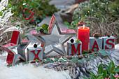 Moderne Weihnachtsdekoration mit Sternen, Kerze und Botschaft XMAS