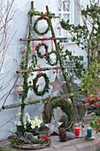 Weihnachtlich dekorierte Terrasse mit Kränzen, Sternen, Zapfen und Lichtern an selbstgebautem Gestell aus Ästen