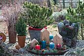 Adventsdekoration mit Kerzen, Holzstücken, Zapfen und Tannenspitzen auf Tablett, Korb mit Zapfen
