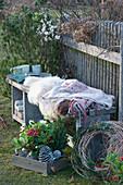 Bank mit Fell und Decke als Sitzplatz am Gartenzaun
