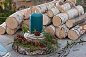 Kerze mit Wollschnur und Zweigen mit Zapfen auf Holzscheibe