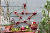 Stern aus Zimtstangen mit Kugeln, Zapfen und Kerze als Weihnachtsdeko