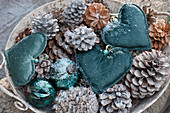 Schale mit Herzen, Zapfen und Kugeln als weihnachtliche Dekoration