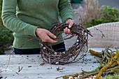 Schneeglöckchen in Kranz aus Zweigen : Frau windet Kranz aus Zweigen von Birke und Weide