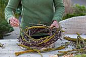 Schneeglöckchen in Kranz aus Zweigen : Frau windet Kranz aus flechtenbewachsenen Zweigen, Birke und Weide