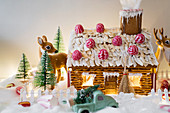 Decorated gingerbread house with deer figurines and lights
