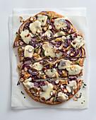 Buckwheat schiacciata with onions, taleggio cheese and hazelnuts