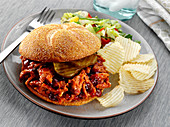 Shredded BBQ Pork with pickles on a Kaiser Roll bun served with potato chips and salad