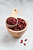 Dried barberries in a wooden bowl and a wooden scoop