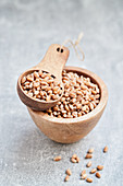 Wheat grains in a wooden bowl and a wooden scoop