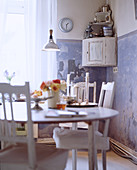 Shabby-chic dining table and chairs in front of blue-and-white wall with patina