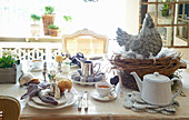 Table set for Easter breakfast with hen ornament in nest