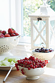 Summer fruits in bowls and colander on windowsill