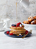 A stack of pancakes served with summer berries and syrup